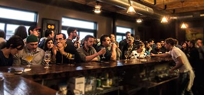 A crowd at the bar in the Logboat taproom