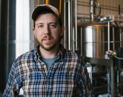 Josh Stacy, co-owner of Public House Brewing, standing in front of beer tanks at the brewery.