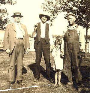 Sepia-toned photo of three men and a young girl posing outdoors