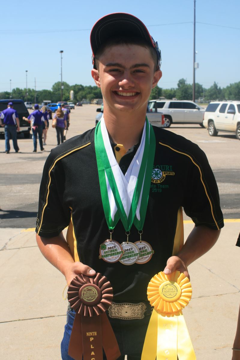Member shows off medals and ribbons from the National 4-H shooting sports competition