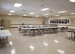 Large meeting room with long tables and many chairs