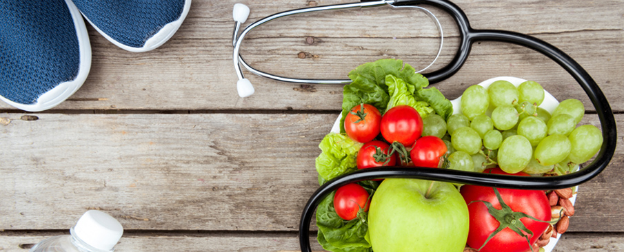 Stethoscope and healthy food on a wooden table