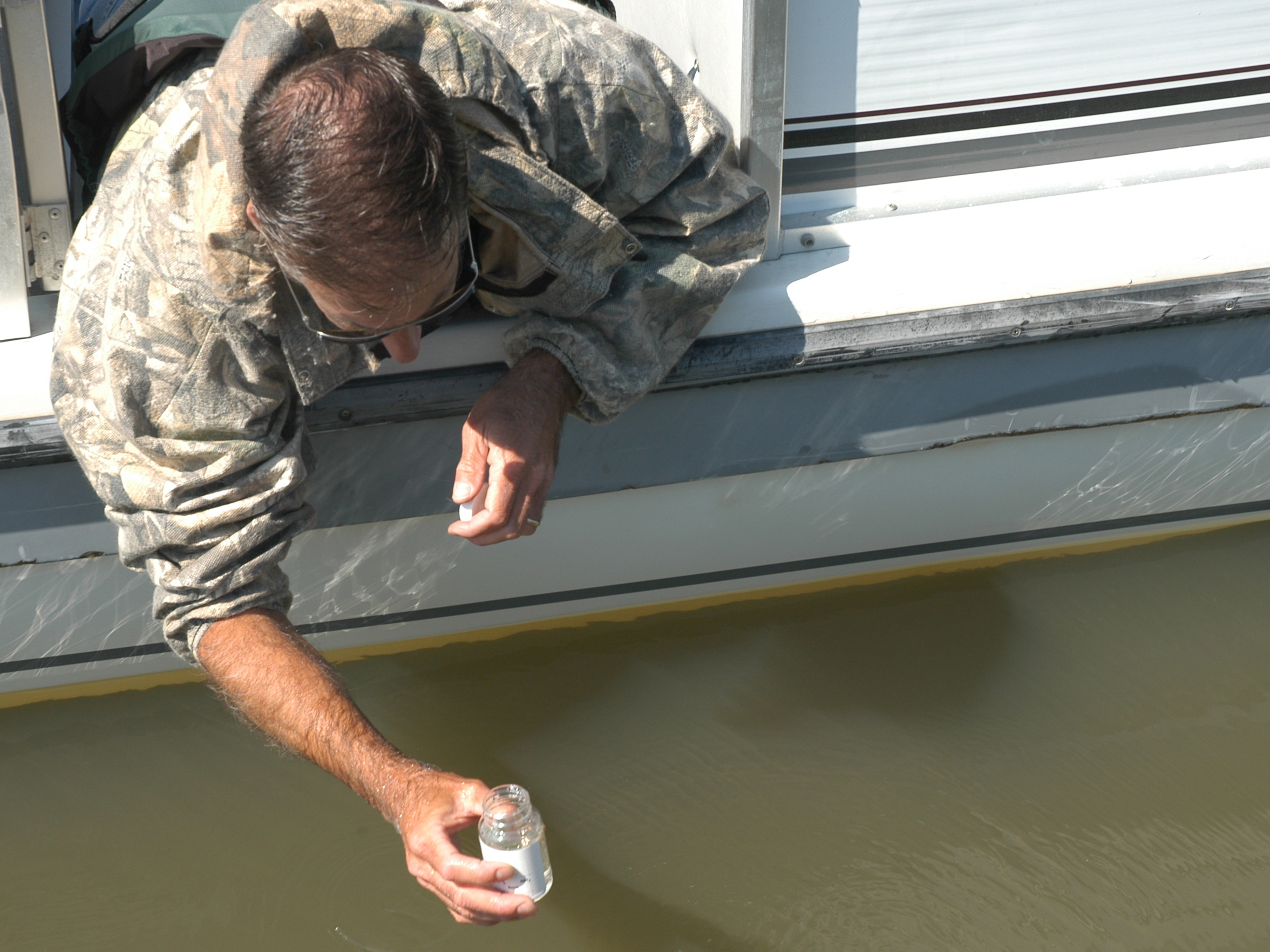 Greg Stoner, a state fisheries management biologist and advisor to the Lake of the Ozarks Watershed Alliance, collects a water sample from one of the lake's many coves.