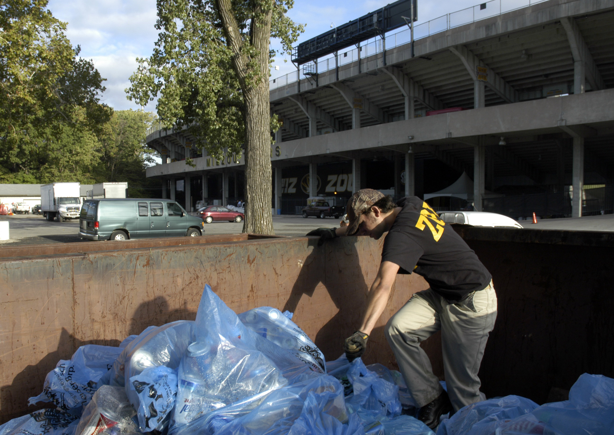 Andrew Daniels, first-year graduate student in parks, recreation and tourism, collects recycling bags from a dumpster behind Memorial Stadium the morning after the Sept. 13 home game against Arizona State. The game generated several tons of recyclable was