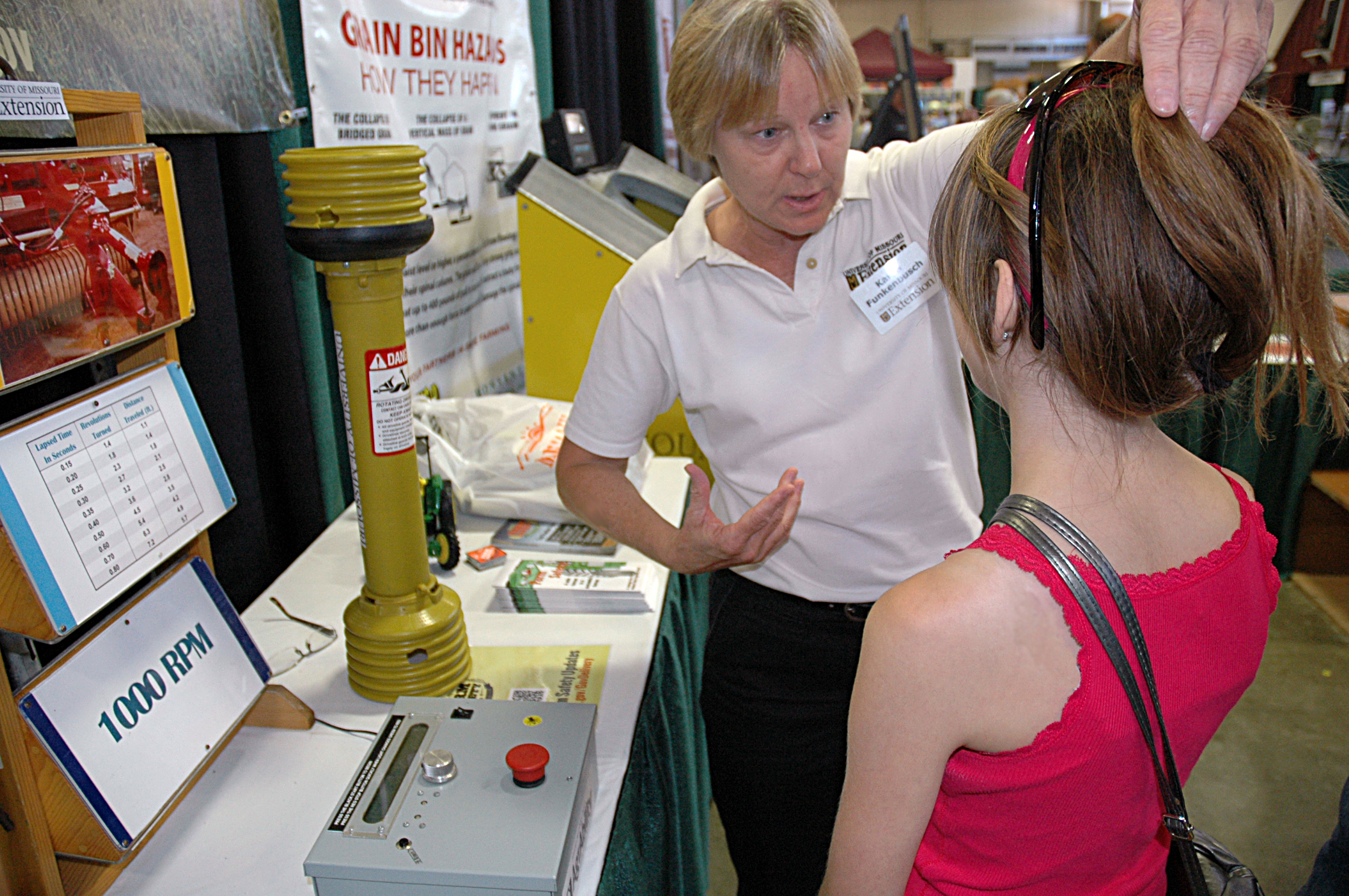 During the 2014 Missouri State Fair, MU Extension safety specialist Karen Funkenbusch tells a young woman that she should pull her long hair up and under a hat when working around farm equipment, especially power takeoff devices that can quickly grab hair