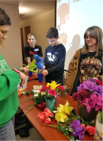 Rankin, left, teaches a floral design workshop to Camp CA-POW participants. Each of the campers had the opportunity to create their own arrangements.