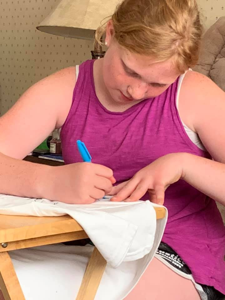 Mattalie, 11, of Saline County, decorating her 'Party in the USA' themed T-shirt, a Heit's Point 4-H camp tradition.