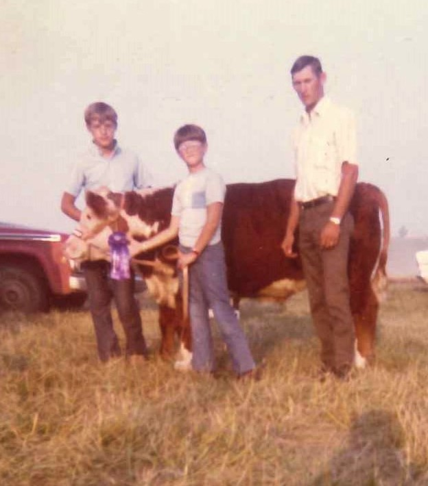 Mike Kateman, center, with his prize-winning calf, Boots. Also pictured: Kateman's cousin Doug Boland, left; and Kateman's father, Donald Kateman.