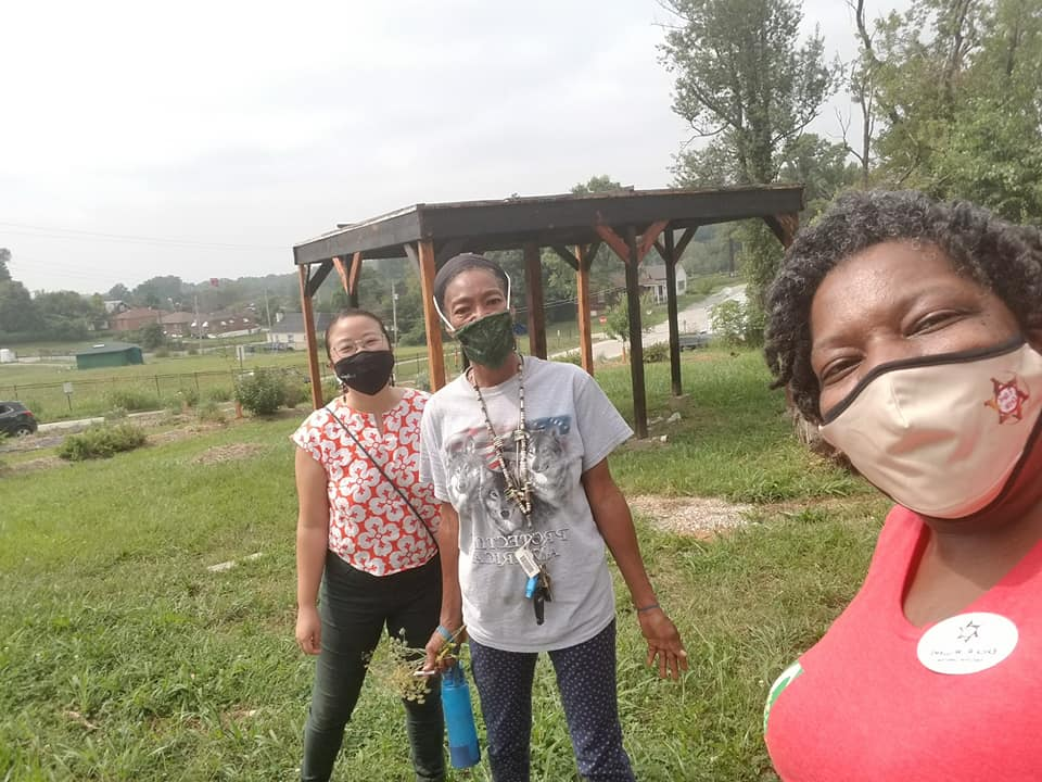 Julia Ho, left, of Solidarity Economy St. Louis and Saundi Kloeckener, center, of Native Women's Care Circle help Erica Williams, right, tend the gardens at the North County Agricultural Education Center. Photo courtesy A Red Circle.
