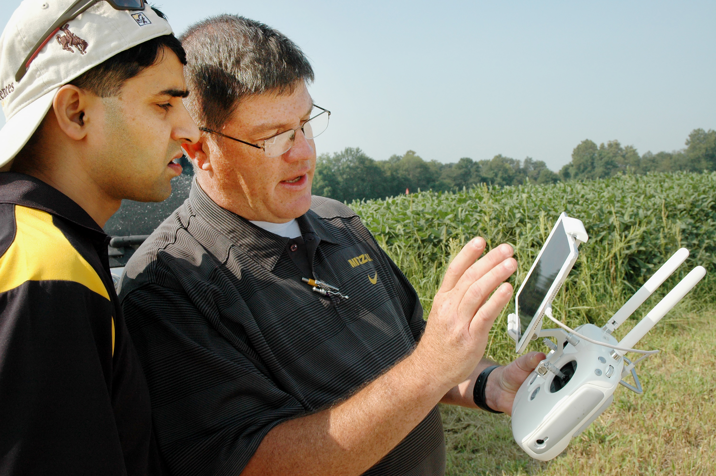 Kent Shannon, right, profiled by Successful Farming magazine's November 2017 issue as an 'exceptional extension specialist,' shows agronomy specialist Dhruba Dhakal how to use a drone to take aerial images of a soybean field in the Missouri Strip Trial Pr