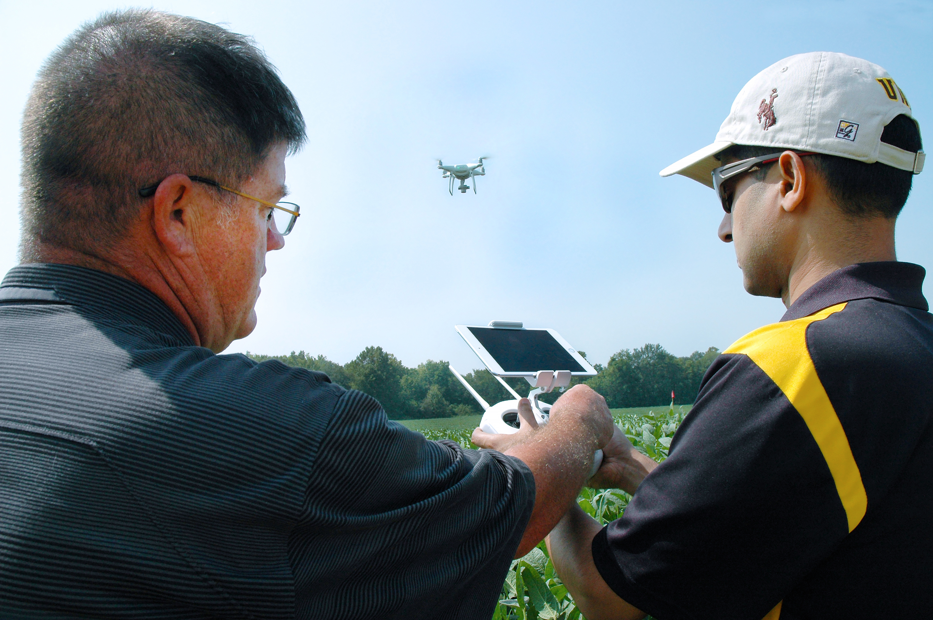 Kent Shannon, left, profiled by Successful Farming magazine's November 2017 issue as an 'exceptional extension specialist,' shows agronomy specialist Dhruba Dhakal how to use a drone to take aerial images of a soybean field in the Missouri Strip Trial Pro