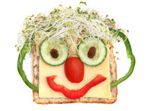 Face made of fruit and veggies on bread
