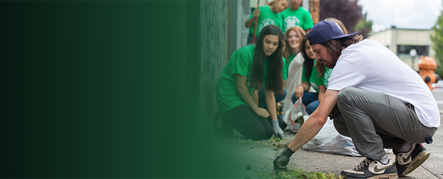 An adult 4-H volunteer instructs 4-H youth during a street cleaning project.
