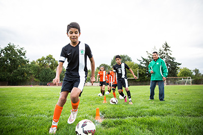 Youth practicing soccer while a coach watches