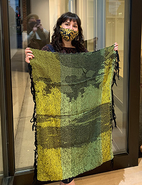 A woman holds an artistic blanket that will be displayed in an empty storefront window