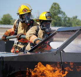 Two firefighters battling a vehicle fire.