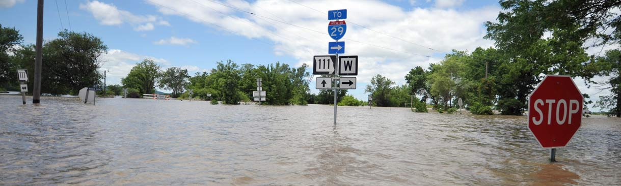 Flooded street with stop sign just visible above water.