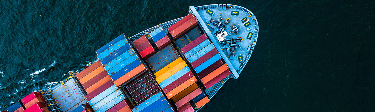 An arial view of a shipping container ship at sea. Its deck is full of shipping containers.