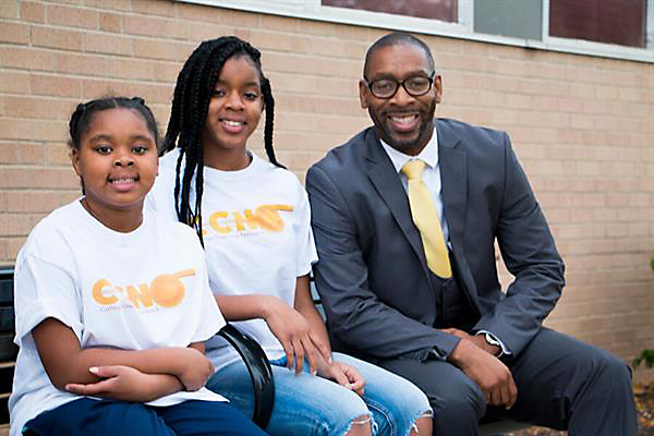 Claude Harris, founder of College Coaching Network, poses with two students