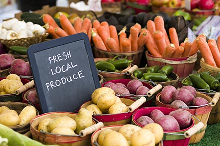 Fresh local produce including carrots, peppers, onions and potatoes.