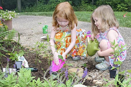 Two young girls working in a backyard habitat: one is digging while the other watches holding a watering can.