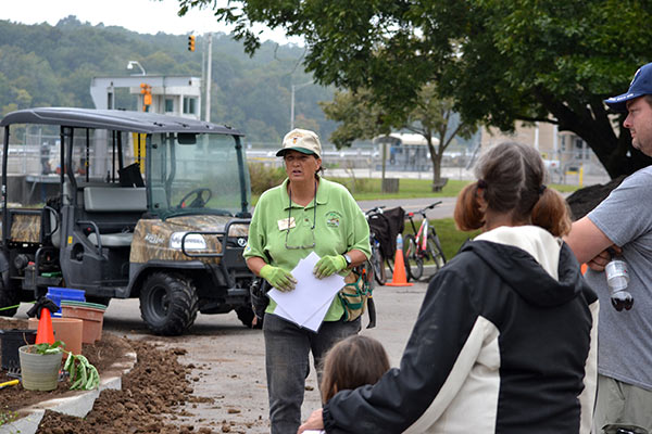 A Master Gardener teaching volunteers about pollinator gardening during an outdoor public event.